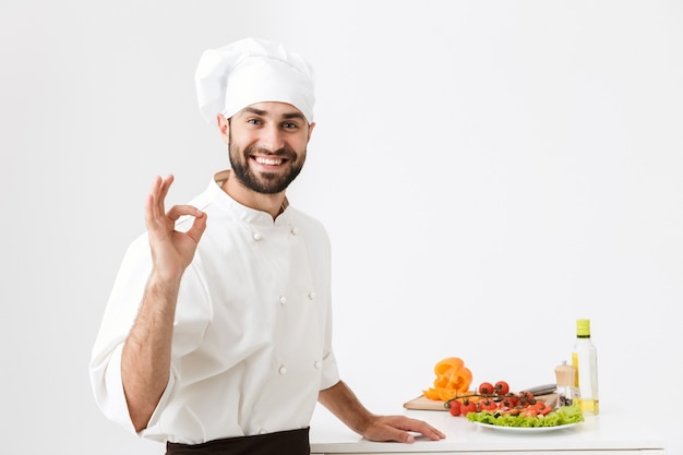 Happy chef man in cook hat smiling and showing delicious sign while posing with vegetable salad at work isolated over white wall