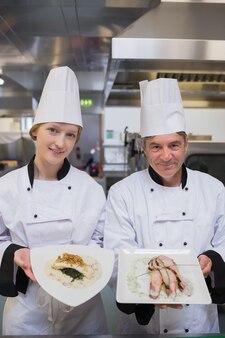 Happy chef's presenting chicken dishes