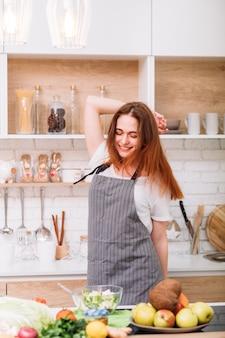 행복한 요리사. 비밀 레시피 재료. 준비된 샐러드를보고 흥분 웃는 여성.