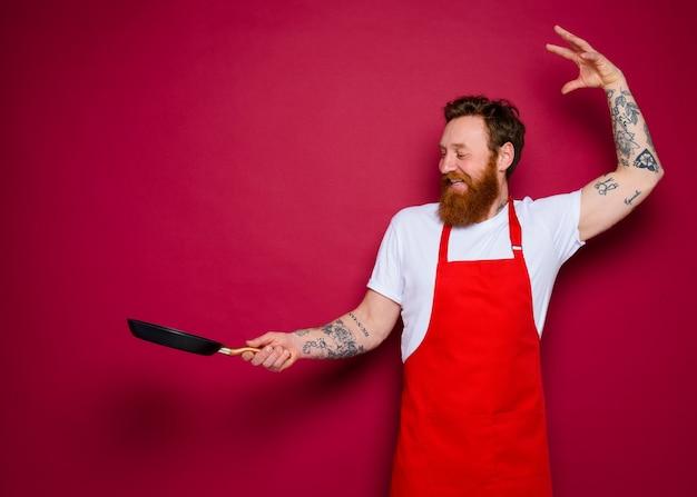 수염과 빨간 앞치마를 가진 행복한 요리사는 팬으로 요리합니다
