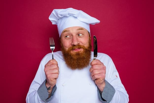 수염과 빨간 앞치마를 가진 행복한 요리사는 칼 붙이를 손에 들고
