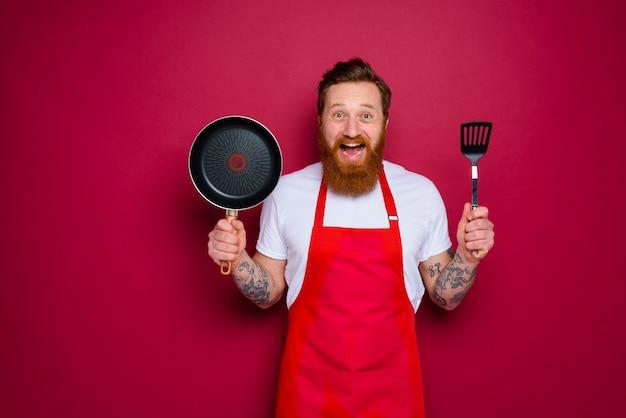 수염과 빨간 앞치마가있는 행복한 요리사가 요리 할 준비가되었습니다.