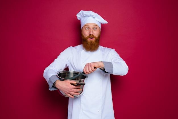 수염과 빨간 앞치마를 가진 행복한 요리사가 요리할 준비가 되었습니다