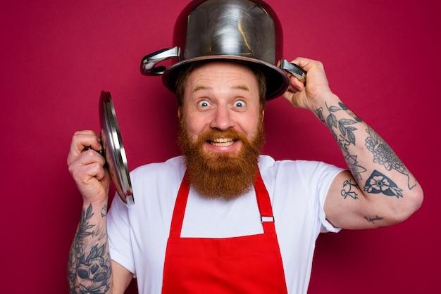 수염과 빨간 앞치마를 가진 행복한 요리사가 냄비를 가지고 노는