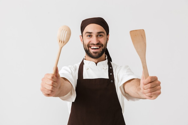 Happy chief man in cook uniform smiling while holding wooden kitchen appliances isolated over white wall