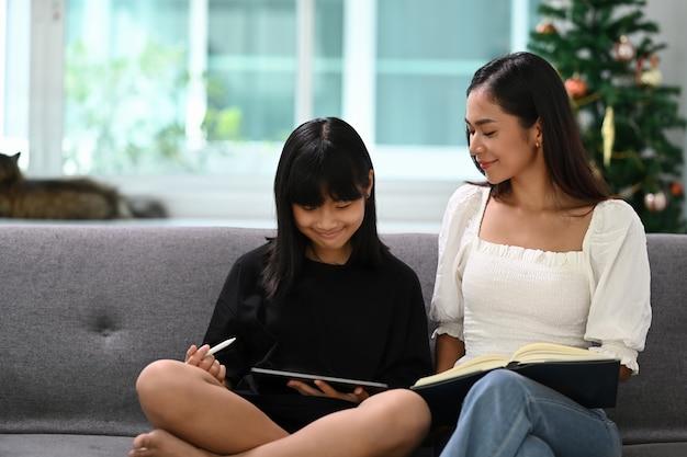 幸せな子供と大人はソファに座って、自宅でデジタルタブレットを使って宿題やオンライン教育を行っています。