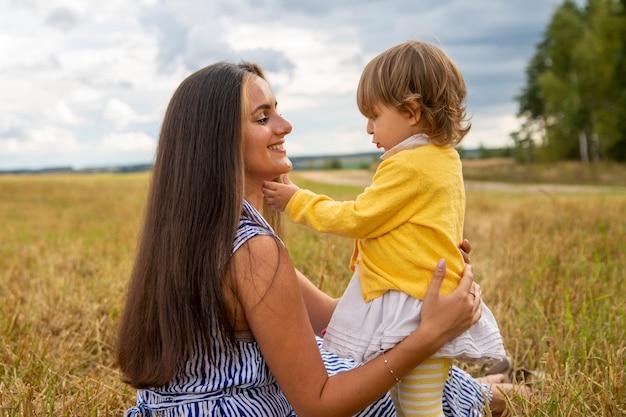 幸せな子供とお母さんはフィールドで屋外で楽しんでいますお母さんと子供は母の日のコンセプトを抱きしめてキスします