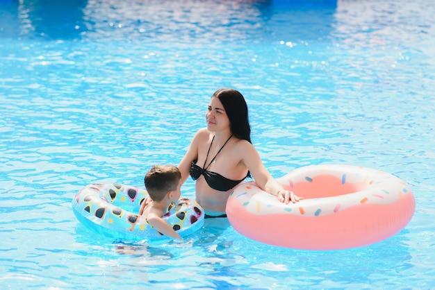 インフレータブルとプールで遊ぶ幸せな子供と女性