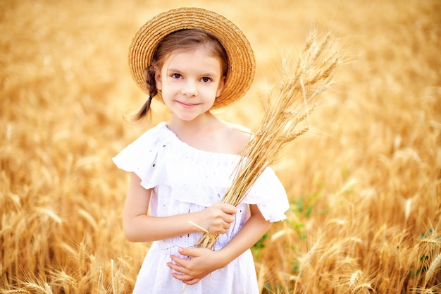 Happy child in autumn wheat field. beautiful girl in white dress and straw hat have fun with playing, harvesting