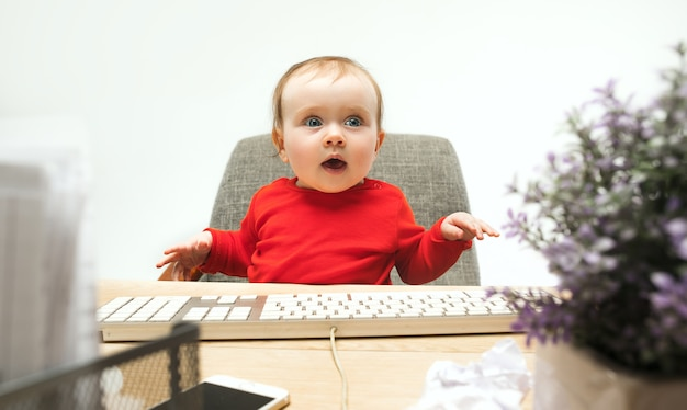 Happy child baby girl sitting with keyboard of modern computer or laptop isolated on a white studio