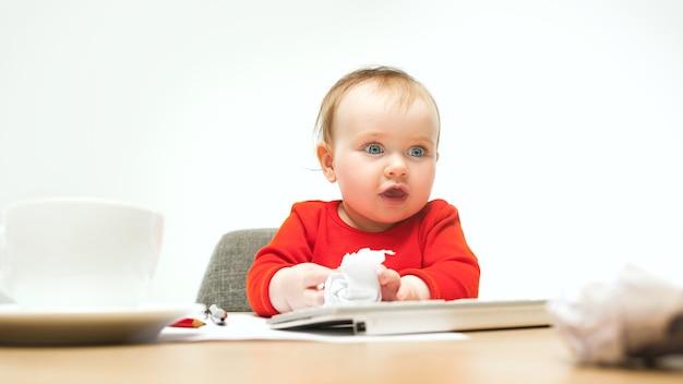 Neonata felice del bambino che si siede con la tastiera del calcolatore o del laptop moderno isolata su uno studio bianco