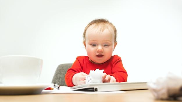 Neonata felice del bambino che si siede con la tastiera del calcolatore o del laptop moderno isolata su uno studio bianco.