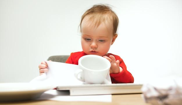 Neonata felice del bambino che si siede con la tastiera del computer o del laptop moderno in studio bianco