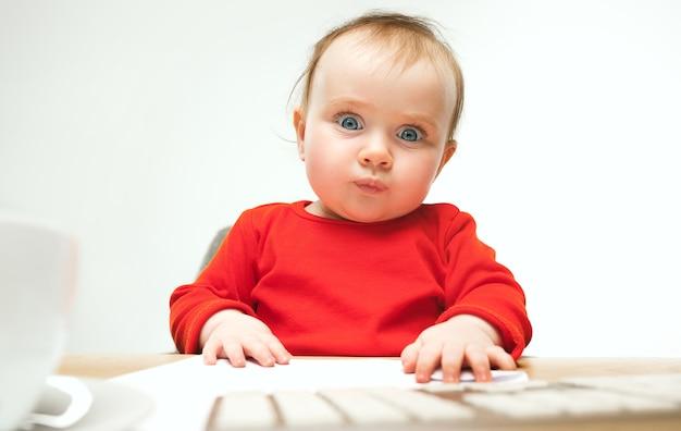 現代のコンピューターのキーボードまたは白いスタジオでラップトップで座っている幸せな子供女の赤ちゃん
