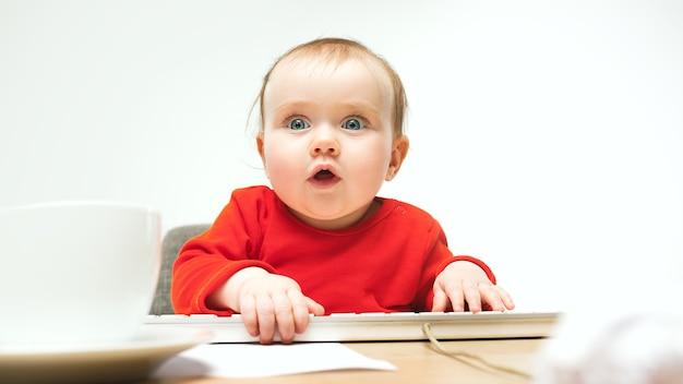 Счастливый ребенок девочка сидит с клавиатурой современного компьютера или ноутбука в белом