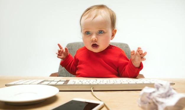 행복 한 아이 아기 소녀 흰색 스튜디오에 고립 된 현대 컴퓨터 또는 노트북의 키보드와 함께 앉아