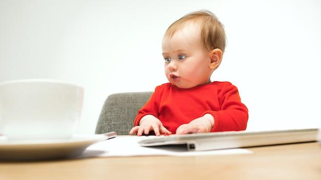 현대 컴퓨터 또는 흰색 스튜디오에 고립 된 노트북의 키보드와 함께 앉아 행복 한 아이 아기 소녀.