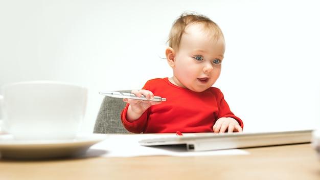白いスタジオで隔離の現代のコンピューターまたはラップトップのペンとキーボードで座っている幸せな子女の赤ちゃん