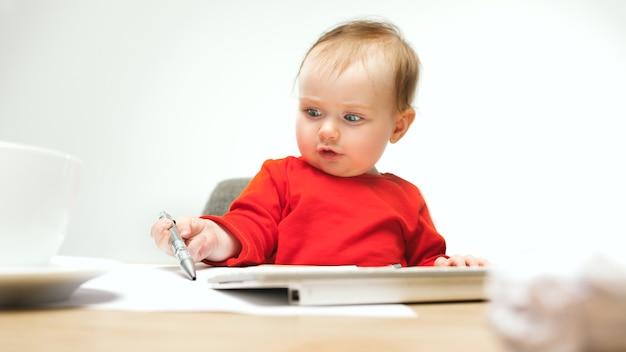 Neonata felice del bambino che si siede con la penna e la tastiera del calcolatore o del laptop moderno isolato su uno studio bianco.