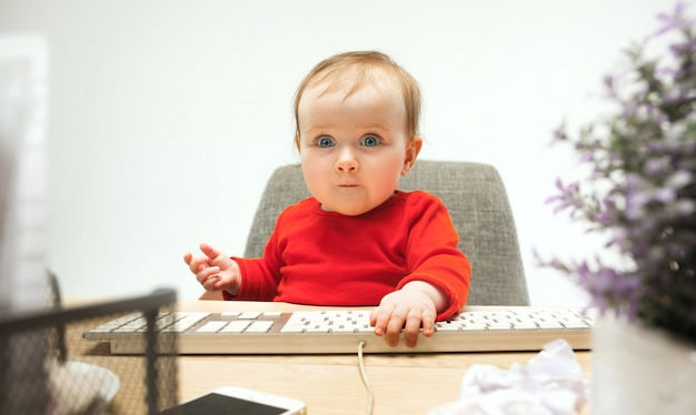 Happy child baby girl toddler sitting with keyboard of computer isolated