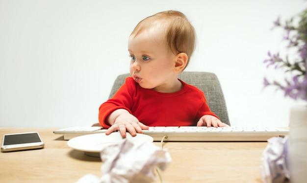 Bambino felice della neonata del bambino che si siede con la tastiera del computer su un bianco