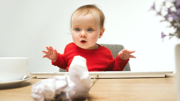 Счастливый ребенок девочка малыша, сидя с клавиатурой компьютера, изолированные на белом
