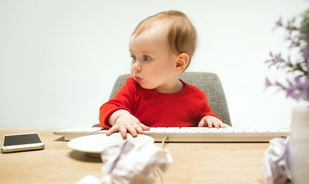 白のコンピューターのキーボードで座っている幸せな子供赤ちゃん女の子幼児
