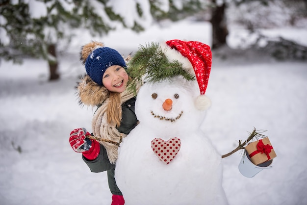Happy child blonde cute girl plaing with a snowman on a snowy winter walk