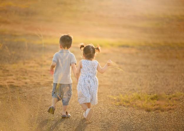 幸せな子供の男の子と女の子の全体的に日当たりの良いフィールド、夏のアウトドアライフスタイル、居心地の良い気分で遊んで