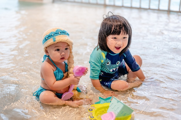 Счастливый ребенок мальчик и маленькая девочка, играя игрушку в бассейне