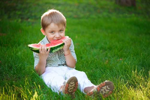 Happy child boy eats watermelon in the summer
