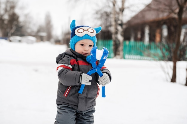 Happy child boy happily playing in the winter snowballs and smiling