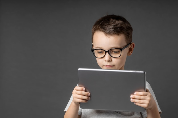 青い背景の上のあなたの情報のためのタブレットipadeを保持している幸せな子供の男の子