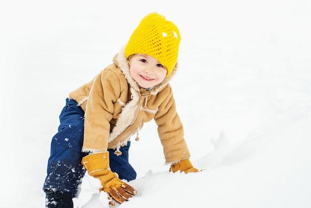 自然の中で冬の散歩で遊ぶ幸せな子供の男の子。雪と冬のフィールドで楽しんで幸せな子供