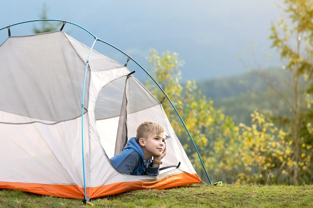 Happy child boy resting in a tourist tent at mountain campsite enjoying view of beautiful summer nature. hiking and active way of life concept.
