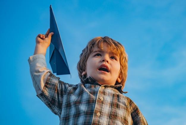 자연 속에서 여름에 장난감 비행기와 초원에서 실행하는 행복 한 아이 소년. 귀여운 소년 재생