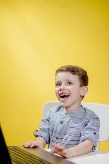 행복 한 아이 소년 노트북 테이블에 앉아 노란색 벽에 학교를 준비합니다. 온라인 학습. 온라인 학교.