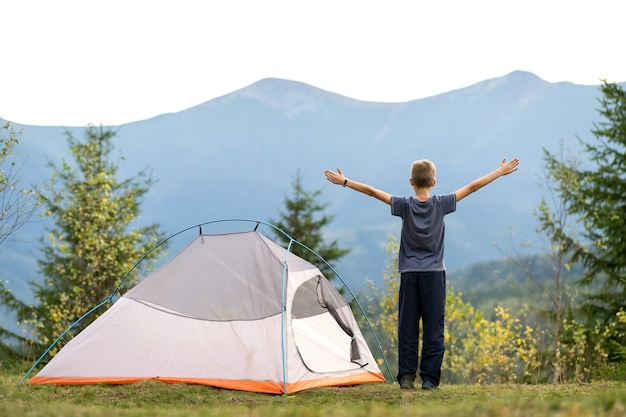 Happy child boy standing with raised hands near a tourist tent at mountain campsite enjoying view of beautiful summer nature. hiking and active way of life concept.