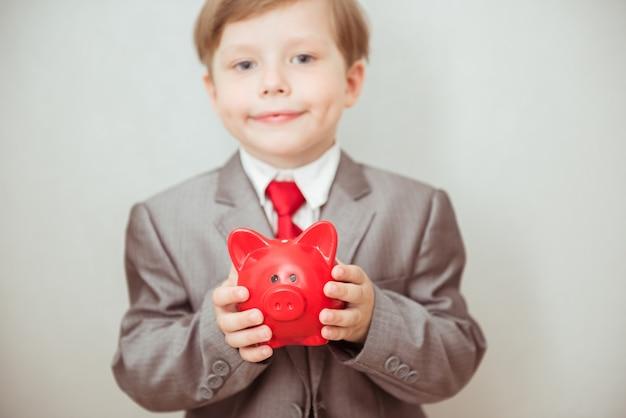 幸せな子供男の子は彼の手に貯金箱を持つファッショナブルなスーツで立っています。成功、創造、革新のビジネスコンセプト
