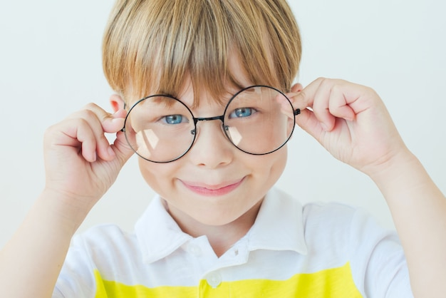 Счастливый ребенок мальчик в очках на белом фоне