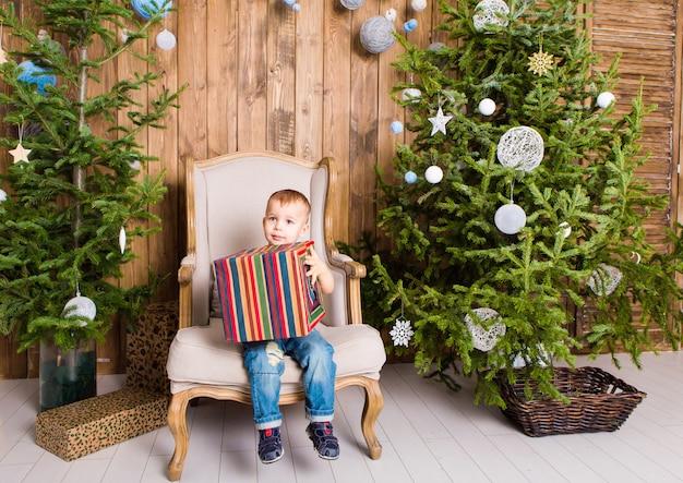 クリスマスツリーの近くのギフトボックスと幸せな子少年。