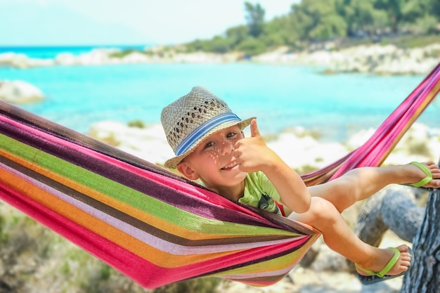 Happy child by the sea on hammock