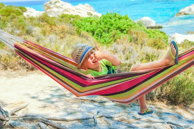 Счастливый ребенок на берегу моря на гамаке на фоне греции
