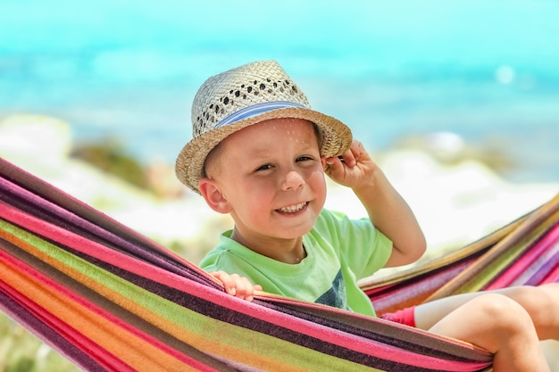 Счастливый ребенок на берегу моря в гамаке