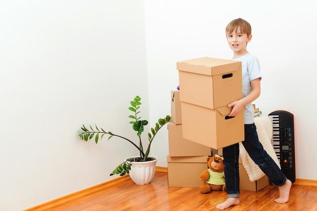 新しい家に箱を運ぶ幸せな子供。引っ越しの日。引っ越しの日を楽しんでいる幸せな少年。子供と一緒に若い家族を収容する。家族は新しいアパートに引っ越します。箱を開梱するのを手伝ってくれるかわいい子供。