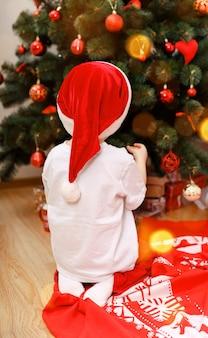 Счастливый ребенок украшает елку шариками в канун рождества