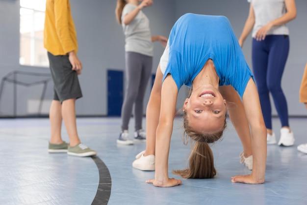 Счастливый ребенок делает позу гимнастики