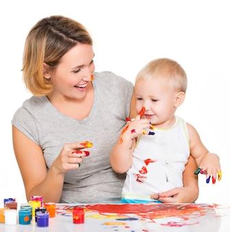 Il bambino felice disegna sul volto di sua madre isolato su bianco.
