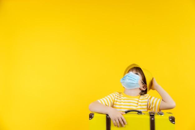 휴가를 꿈꾸는 행복한 아이. 실내 보호 마스크를 착용하는 아이의 초상화입니다.