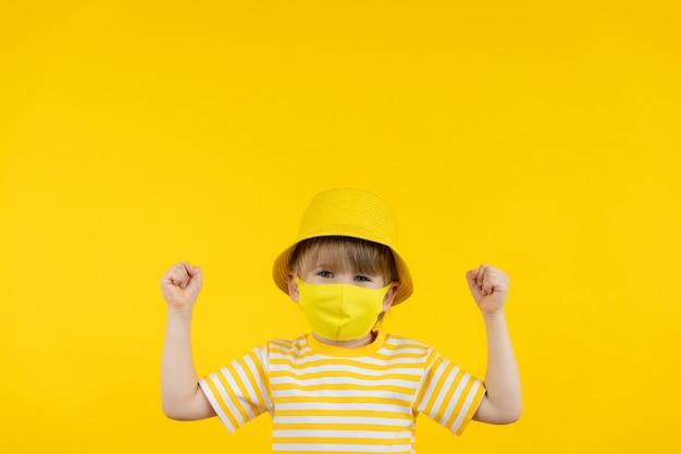 休暇を夢見て幸せな子。屋内で保護マスクを着用している子供の肖像画。